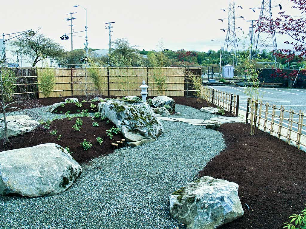 Japanese Rock Garden With Japanese Garden Rock Lanter And Bamboo Fencing.